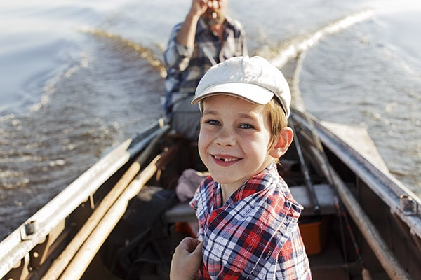 Caucasian boy smiling at camera while in a boat