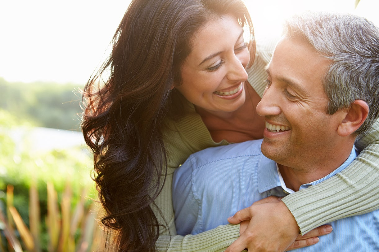 Middle aged man and woman smiling and hugging